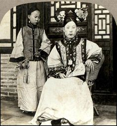 A high caste Manchu lady attended on by her maid who holds her pipe inches from her mouth. Both have long fingernails on the last two fingers of their hands, covered with fingernail protectors.