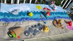 unrolled felt beach scene, figures swim, build a sand castle, cover up with sand and build in the sand.