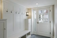 - white built-ins slate tiles floor  Great mudroom with white built-ins and slate tiles floor.