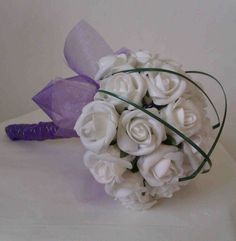 Pretty Posey of soft White Foam Roses with a cage of Bear Grass, wrapped in Cadburys Purple Organza £25...available in all colours of flower & organza..