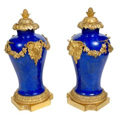 "PAIR ORMOLU MOUNTED LAPIS LAZULI URNS:    Baluster form decorated with applied floral swags, and rams head masks, and fitted with a lid and base all in gilt bronze. 18""H X 11""W"