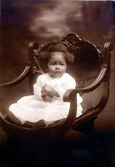 This photo is a beautiful gem from the past. Beautiful baby and chair.