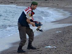 The body of three-year-old Syrian refugee Aylan Kurdi, is cradled by a police officer in Turkey, having washed up on a beach.