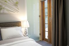 modern frosted glass door next to french doors in master bedroom leading to ensuite