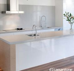Caesarstone benches and splash back.  Nice bench island colours with wooden floor.