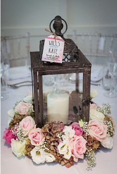 Wedding centrepiece lanterns with pillar candles wrapped with a mix of blush pink roses and gym at Old Brook Barn
