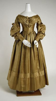 Dress (circa 1838)  The Metropolitan Museum of Art.  This lovely dress has knife pleats across the hips, which falls from the v-point bodice.  Accent band of slightly contrasting gold fabric encircles the skirt at about knee height.