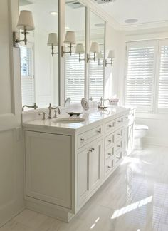 """Artistic Tile I In renovating an historic estate that once belonged to the legendary Scalamandré family, designer Oriana Cyprus chose a palatial blend of our Bianco Dolomiti marble (bath floor) and Calacatta Gold """"Studs"""" mosaic (shower floor) for the master bath."""