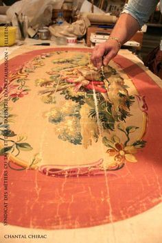An artist measuring an hand painted design that is used by a weaver for making an Aubusson rug.