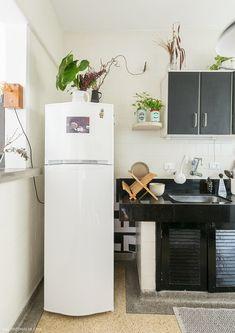 Cozinha antiguinha tem armário preto, bancada de granito na mesma cor e piso de granilite.