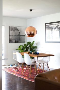 A modern dining room design featuring large black and white artwork, a contemporary copper hanging pendant light, a wood top table with metal legs, white Eames chairs, and a colorful woven area rug - Home Decor & Decorating Ideas. Decoration Inspiration, Dining Room Inspiration, Interior Inspiration, Decor Ideas, Decorating Ideas, Dinning Room Ideas, Craft Ideas, Rug Inspiration, Diy Ideas