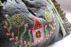 A pretty little house nestled in the garden. Embroidery.