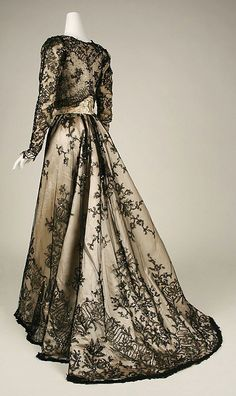 Champagne colored gown.  The skirt is covered in black lace, which pattern is accentuated along the hemline & train.  A small bolero-type jacket, with long sleeves, goes over the bodice