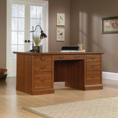 "Camden Country Collection Executive Computer Desk in Planked Cherry Finish by Sauder. $469.98. FeaturesThree file drawers hold letter, legal or European size hanging files and feature full extension slides. Top left file drawer features key lock. Two box drawers on right and center drawer with pencil tray have metal runners and safety stops. Melamine top is heat, stain and scratch resistant and has grommets for cord access. Planked Cherry finish. DimensionsW:65 1/2"" (166..."