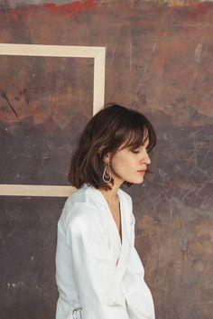 mujer con blusa blanca de perfil, pendientes de plata, cortes con flequillo, flequillo largo media luna despuntado