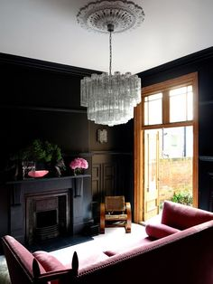 Dark and feminine living room with modern glass chandelier, pink sofa, and black painted walls and fireplace.