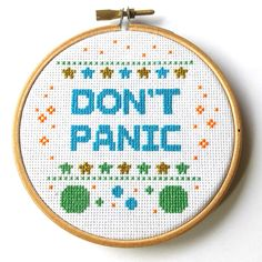 This listing is for a finished item. This Dont Panic Hitchhikers Guide to the Galaxy cross stitch is framed in a four inch wooden embroidery hoop.