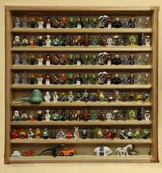 """Made-to-order, handcafted display case for Lego Minifigs.  The case pictured is 24"""" x 24"""" (2ft x 2ft) and will hold about 150 regular-sized minifigures.  Each shelf is lined with permanent Lego studs to hold the minifigs in place.  This is a top-quality, hand-made shelf, made in the USA out of expensive wood and can be made in natural oak (pictured) or stained/painted to any color you wish.  http://www.ayrow.com/woodwork.htm"""
