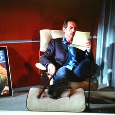 And here he is, Hugh Laurie reading in his Eames lounge chair and ottoman in the TV show House.