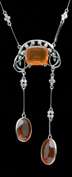 A fire opal set necklace, attributed to Archibald Knox, circa 1900-1904, the central cushion-shaped fire opal enclosed by diamond points, within a bridge of Celtic entrelacs, suspending two knife-edge batons below, spaced with rose-cut diamond highlights and terminating with oval mixed-cut fire opals drops,