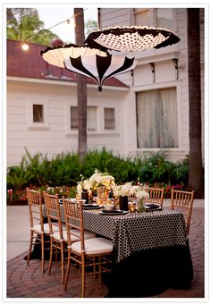 umbrellas parasol outdoor decor for dinner party outside. Love the pretty black and white parasol suspended over pretty table setting in courtyard. Best Patio Umbrella, Table Umbrella, Umbrella Lights, Outdoor Dining, Outdoor Decor, Outdoor Lighting, Patio Dining, Outdoor Seating, Gardens