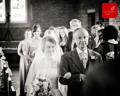 Bride with veil and lace detail dress arriving at the front of the church with her father www.grahamcrichton.com
