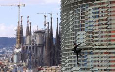 """French urban climber, Alain Robert, also known as """"French Spiderman"""", right, scales the 145 meters of the Agbar tower with the La Sagrada Familia Basilica designed by architect Antoni Gaudi in the background."""