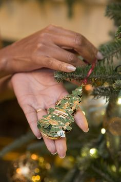 First Lady Michelle Obama holds the White House Historical Association Christmas ornament, showing off the back of the 2015 ornament, as she hangs it on a tree in the Diplomatic Reception Room of the White House on Dec. 10, 2015.