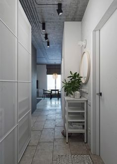 The hallway and entrance area offers a breathing space before the main area, while still following the same theme. Circles form mirrors and art on the walls, while the white backdrop affords space for the unique branched coat rack.