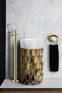 Koi is a round and single freestanding with a structure made of aged brushed brass. Since it uses a scale pattern based on the koi carp, it gives, somehow, an optical illusion of a meshwork. It features a countertop sink made of Nero Marquina marble.