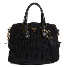 This is an authentic PRADA Tessuto Nylon Gaufre Tote in Nero Black.  This chic tote is crafted of fine tessuto multi-pleated multi-tiered nylon.  The bag features rolled leather top handles with bold gold links and buckles and an optional shoulder strap with gold clasps.  This opens to a spacious Prada jacquard monogram fabric interior with zipper pocket.  This is a marvelous tote, ideal for everyday use, only from Prada!