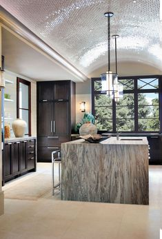 The tiny mosaic tiles on this barrel-vaulted ceiling defines this space. The dramatic overhead curve creates a stunning centerpiece matched only by the waterfall granite countertops from Walker Zanger that outfits the main island.