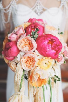 A gorgeous #wedding #bouquet made with peonies, garden roses and ranunculus in #pink #peach and #yellow