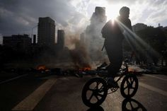 Venezuela opposition on the streets:     A DEMONSTRATOR RIDES HIS BICYCLE NEAR A FIRE BARRICADE DURING A RALLY IN CARACAS, VENEZUELA  A demonstrator rides his bicycle near a fire barricade during a rally.  -  April 10, 2017