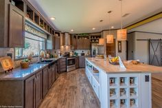 The wine storage and the outlets in the island are soooo great! Plus the miniature barrel shades around the pendant lights add a modern touch to this classic #kitchen in The Magnum Home 76 ML34764M by Palm Harbor Homes