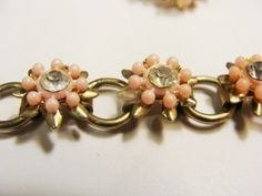 """Here is a matching set of pretty pink flowers accented with clear rhinestones on a gold tone setting.  There is a choker and screw back earrings.  They are unsigned.  The choker is approx. 15 5/8"""" long.  The earrings are approx. 1 1/2"""" long.  They are in good used condition."""