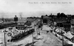 (ca. 1900)* - View of Front Street (now Avalon Boulevard) at San Pedro Harbor showing a multitude of passengers disembarking from a commuter train. Commercial storefronts can be seen acroos the unpaved road to the far right of the photo.