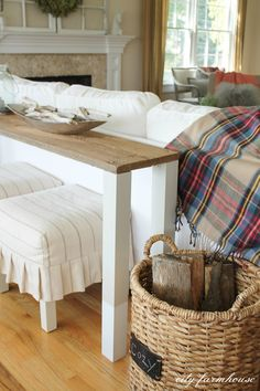 DIY Console Table Using Reclaimed Wood - table behind sofa, stools under, and blankets instead of firewood in the basket.