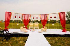 This red and gold drape mandap is more backdrop than enclosure. On top of white covered, black skirted stage. Palki Mandaps, Photographik Studios via Maharani Weddings
