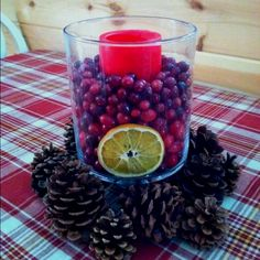 Easy holiday centerpiece -- hurricane candle holder, pillar candle, pinecones, fresh cranberries, orange slices (bake slices in toaster oven for 30min on low heat to dry them out)
