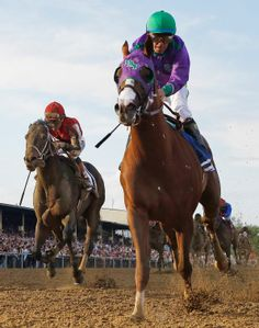California Chrome, front, ridden by jockey Victor Espinoza, wins the 139th Preakness