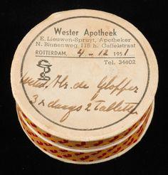 """Kartonnen pillendoos """"Wester Apotheek, Rotterdam"""" met handgeschreven opschrift en geel-rode zijkant"""