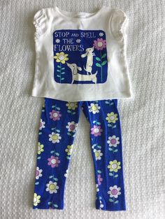 "White short sleeve shirt with wiener dogs and flowers and ""stop and smell the flowers"" print. Gymboree girl's size 2T outfit in excellent used condition with no stains or holes. Blue flower print leggings with an elastic waist. 