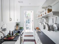 This narrow galley kitchen in Bklyn NY is filled with extra-tall storage & shelving, & the work surface on the right is narrower, with shallow bespoke cabinets underneath, including one housing an extra-small microwave. Counter tops are hard-wearing slate. The original brick wall is painted white as a cheap splashback; walls & cabinets are also white to make the space feel larger. A glazed door leads to an outdoor eating deck.