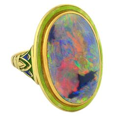 Art Nouveau Enameled Black Opal Gold Ring. An extraordinary black opal ring from the Art Nouveau (ca1900) era! This exquisite ring is made of 14kt yellow gold and holds a single large black opal at the center of a decorative enamel mounting. The opal is bezel set and surrounded by a bright green enamel border. At each shoulder is a decorative pillar design, which is complete with colorful green and blue enamel details. The band of the ring is smooth and tapers in towards the back.