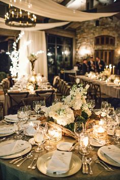White and silver wedding reception table with silver linens, silver chargers and white centerpiece florals in silver and natural wooden vessels at The Farm at Old Edwards Inn and Spa in Highlands, NC. Florals by Uncut Flowers, LLC, image by Vue Photography.