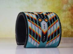 This American Indian beaded bracelet with the classic Cherokee Chevron pattern is made with the blends of the fire colors of the Southwest along with a splash of turquoise. The base used for this brac Chevron Patterns, Bead Loom Patterns, Beading Patterns, Beading Ideas, Beading Projects, Bracelet Patterns, Turquoise Chevron, Beaded Cuff Bracelet, Native Americans