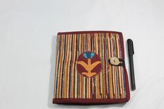 The reusable jute-and-cloth cover of this diary is a striped kalamkari, with a motif embroidered by hand onto the front. There is also a pocket and a tasselled bookmark inside.