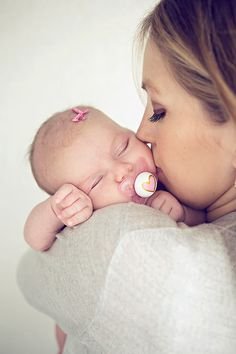 Adorable mom and newborn baby pose for baby pictures