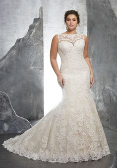 This Mori Lee Julietta 3233 Keri sleeveless plus size wedding gown features an illusion bateau neckline, complementing the button-appliqued illusion back. This fit and flare plus size bridal dress is fashioned in frosted Alencon lace appliques on soft net, flaring to a scalloped hem and chapel train. Available in sizes 16 to 32.